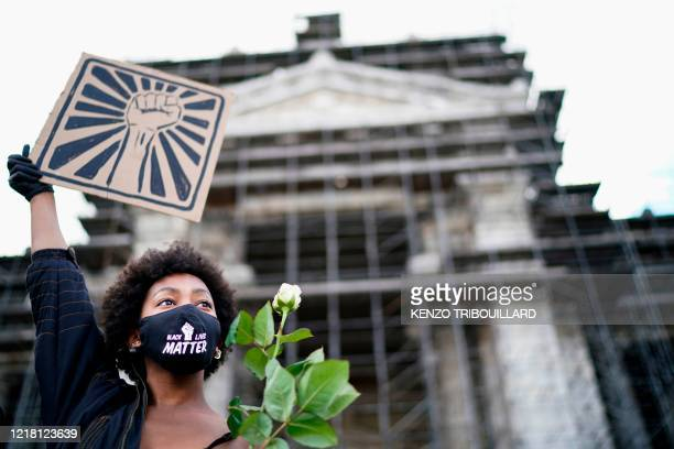 TOPSHOT A woman wears a protective face mask on which is written 'Black Lives Matter' and holds a white rose and a placard depicting a fist during an...