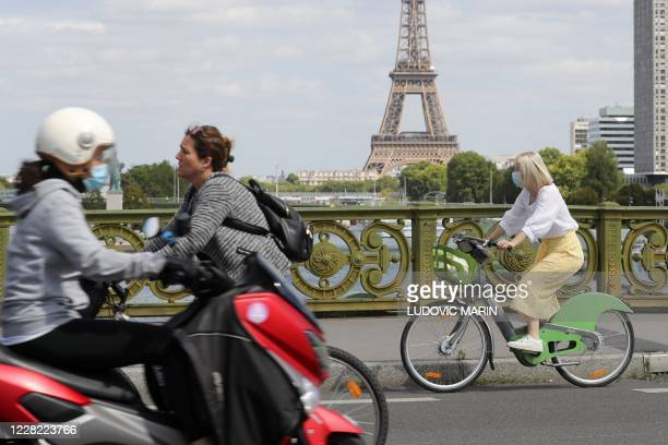 Woman wears a protective face mask while cycling across Pont Mirabeau bridge, near the Eiffel Tower, on August 27 in Paris. - France's prime minister...