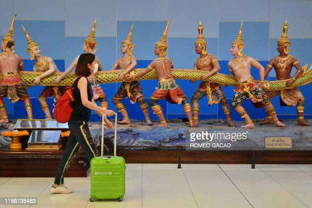 Woman wears a protective facemask as she walks in Suvarnabhumi International Airport in Bangkok on February 5, 2020. - Thailand so far has detected...