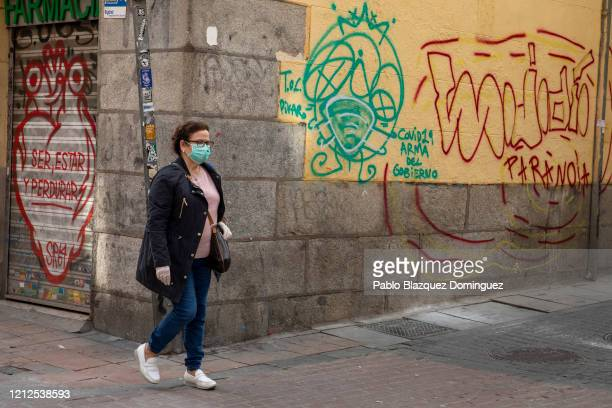 Woman wears a protective mask and gloves as she walks past graffiti which reads 'to be, to stay and to last' , 'Covid19. Government Weapon' and...