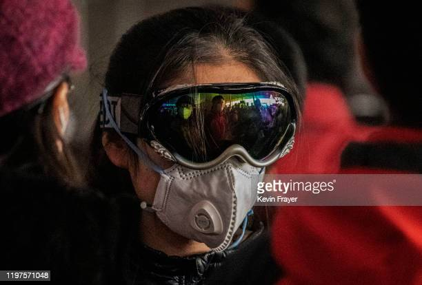 A woman wears a protective mask and ski goggles as she lines up to check in to a flight at Beijing Capital Airport on January 30 2020 in Beijing...