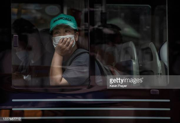 A woman wears a protective mask as she looks out from a bus window during rush hour on July 17 2020 in Beijing China Chinas economy returned to...