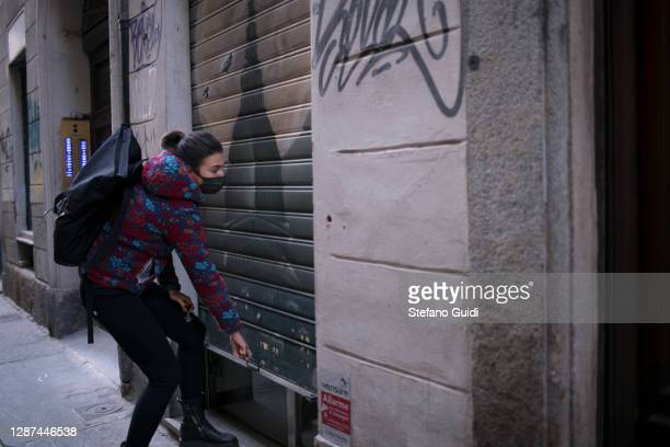 A woman wears a protective mask as she opens the shutter of the doll restoration shop in Via Barbaroux on November 24 2020 in Turin Italy Via...