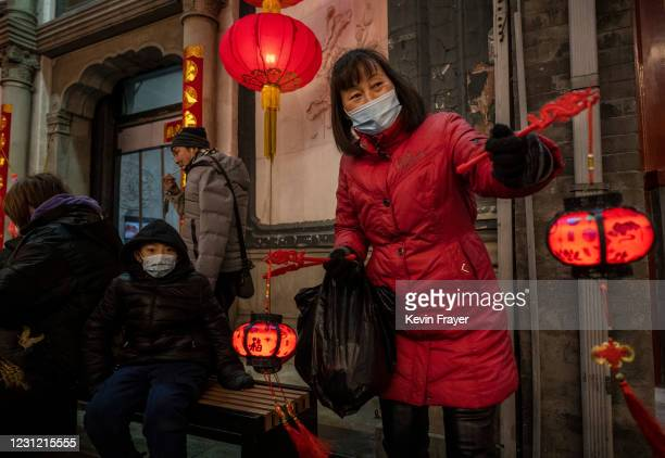 Woman wears a protective mask as she sell red lanterns, or hong denglong, during the Chinese New Year holiday, also known as the Spring Festival,...