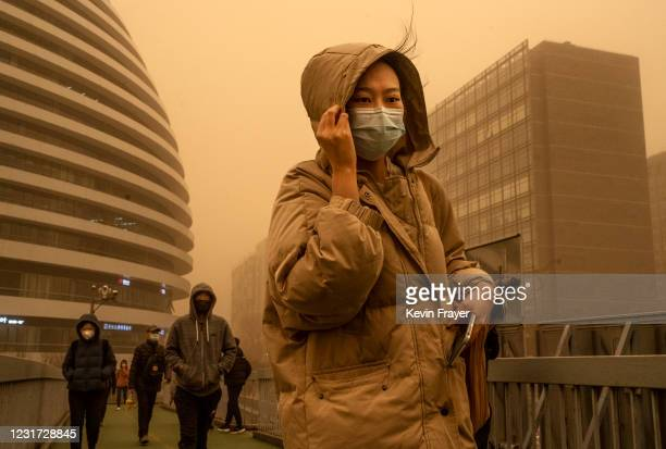 Woman wears a protective mask as she shields herself in heavy winds while commuting during a sandstorm on March 15, 2021 in Beijing, China. China's...