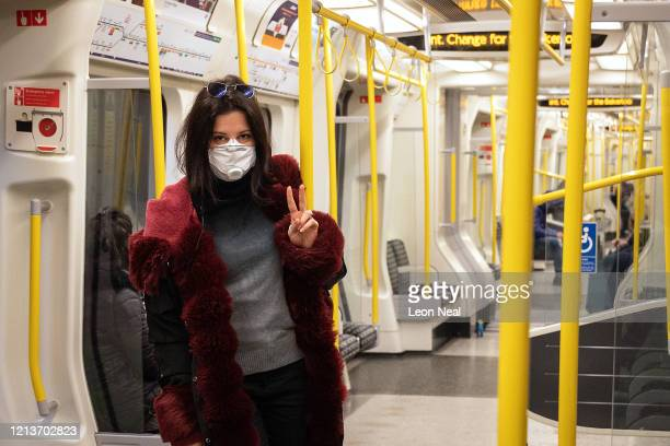 A woman wears a protective mask as she travels on an underground train on March 20 2020 in London England Mayor of London Sadiq Khan has announced...