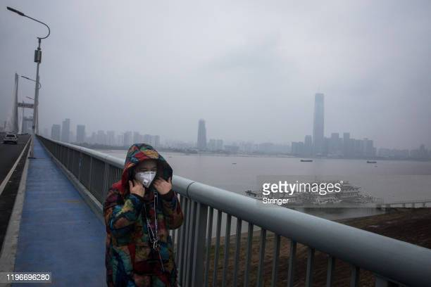 A woman wears a protective mask as she walks across the Yangtze River Bridge on January 27 2020 in Wuhan China As the death toll from the coronavirus...