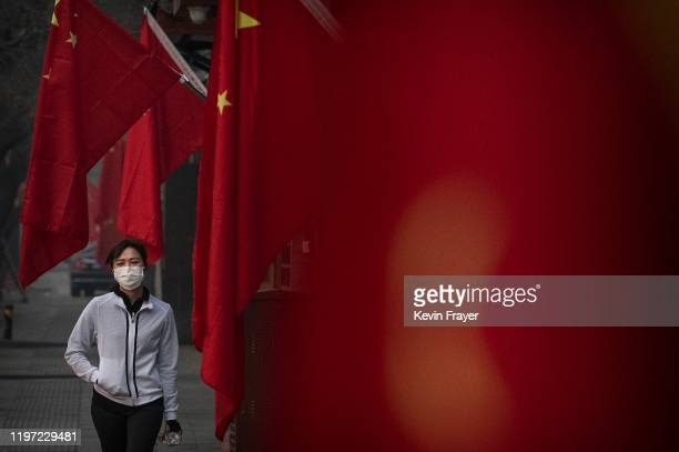 Woman wears a protective mask as she walks by Chinese flags in a street during the Chinese New Year and Spring Festival holiday on January 28, 2020...