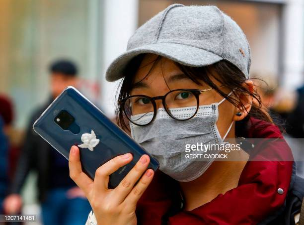 Woman wears a protective mask following the outbreak of the novel coronavirus COVID-19 as she chats on her phone in Cardiff, Wales on March 14, 2020....