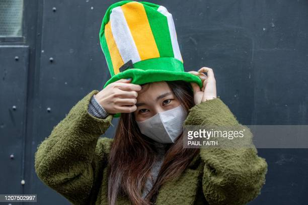 TOPSHOT A woman wears a protective mask in the popular Temple bar area of Dublin on March 17 as St Patrick's Day festivities are cancelled and pubs...