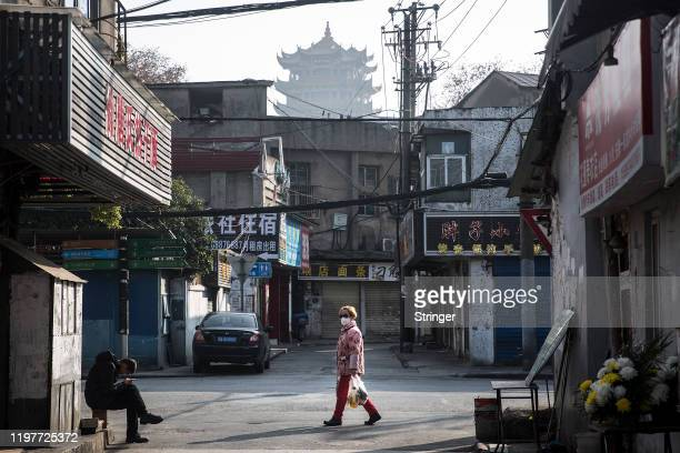Woman wears a protective mask walk in the street as man sit in the roadside on January 31, 2020 in Wuhan, China. World Health Organization...