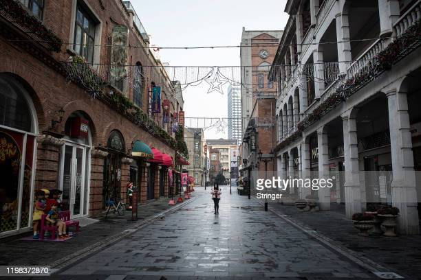 A woman wears a protective mask walks down an empty street on February 3 2020 in Wuhan Hubei province China The number of those who have died from...