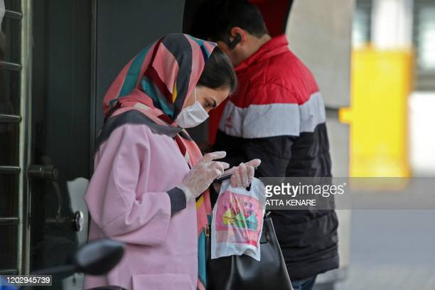 Woman wears a protective mask while using a smartphone as she stands along the side of a street in the Iranian capital Tehran on February 24, 2020. -...