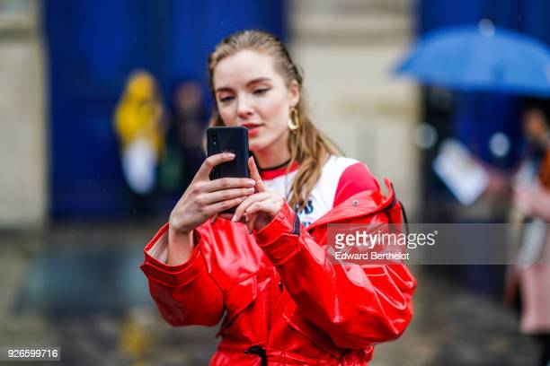 A woman wears a red pvc coat and is using a smartphone to take selfies outside Balmain during Paris Fashion Week Womenswear Fall/Winter 2018/2019 on...