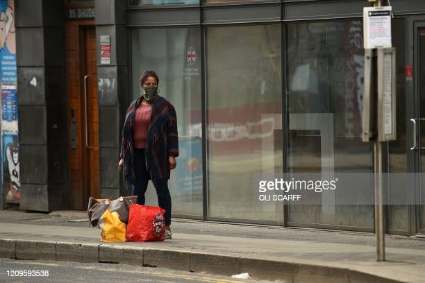 Woman wears a scarf as a protective face mask as she waits with shopping bags in Manchester in north-west England on April 10, 2020 as warm weather...