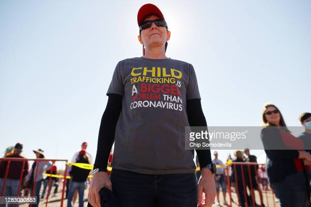 Woman wears a shirt promoting a conspiracy theory promoted by the QAnon group while waiting in line to attend a campaign rally with U.S. President...