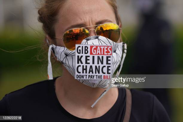 "Woman wears a sign that reads: ""Don't give Gates a chance. Don't pay the bill"" in reference to Bill Gates, who is currently a popular target of..."