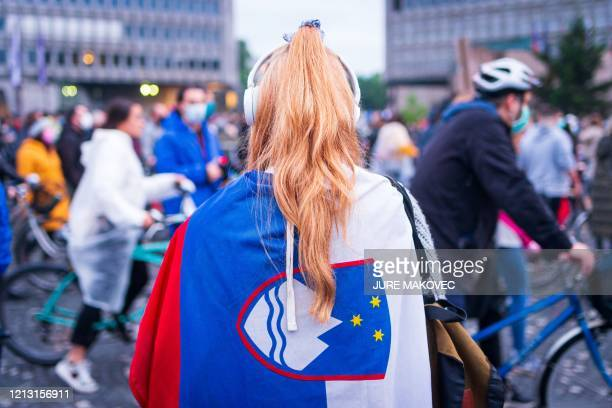 Woman wears a Slovenian flag as protesters, some wearing face masks, stand with their bicycles outside the Slovenian National Assembly building and...