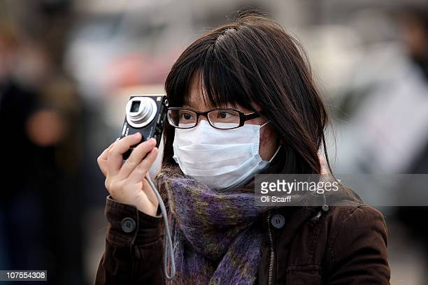 A woman wears a surgical face mask as she takes a photograph in Trafalgar Square on December 13 2010 in London England Britain's Health Protection...