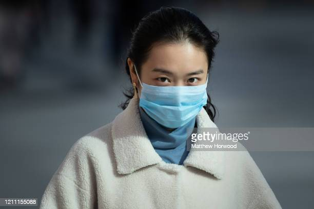 A woman wears a surgical face mask as she walks in the street on March 8 2020 in Cardiff United Kingdom Coronavirus has spread to over 100 countries...
