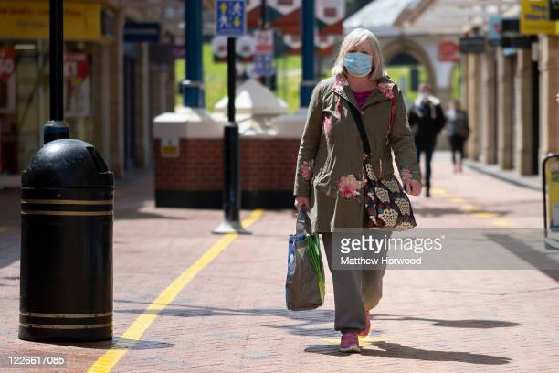 A woman wears a surgical face mask while carrying a bag of shopping in Castle Court shopping centre during the coronavirus lockdown period on May 23...