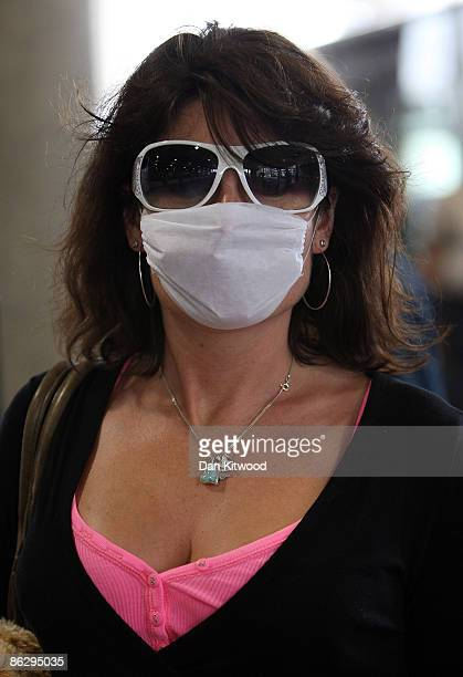 A woman wears a surgical mask after departing a flight from Mexico City at Gatwick Airport on April 30 2009 in London England Airlines and travel...