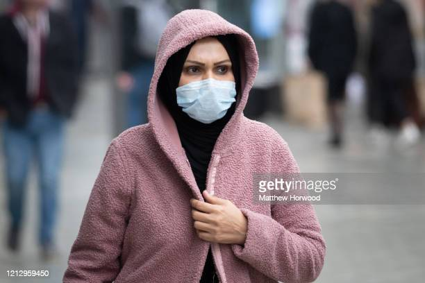 Woman wears a surgical mask on March 17, 2020 in Cardiff, Wales. Boris Johnson held the first of his public daily briefing on the Coronavirus...