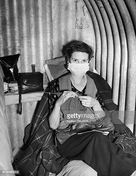 Woman wears a surgical mask to protect others from her cold in a British air raid shelter during World War II.