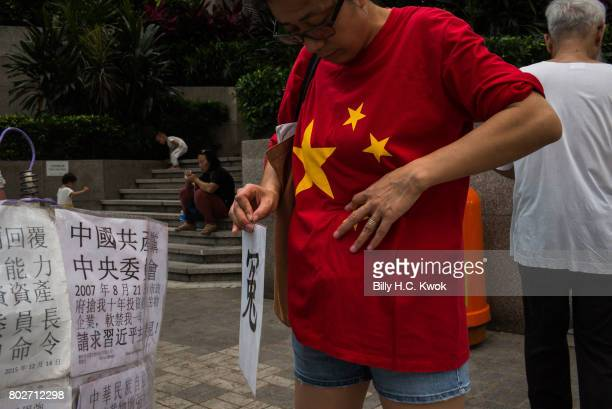 A woman wears a tee shirt of a China flag protesting near the Hong Kong Convention and Exhibition Center ahead of Chinese President Xi Jinping's...