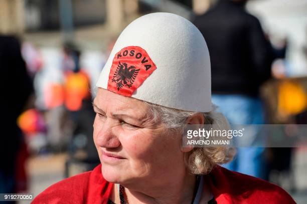 A woman wears a traditional Albanian wool hat with the lettering 'Kosova' and the Albanian eagle as she takes part in celebrations for the 10th...