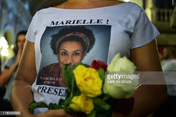 A woman wears a tshirt bearing the portrait of slain Brazilian councilwoman Marielle Franco during a mass celebration on the first anniversary of her...
