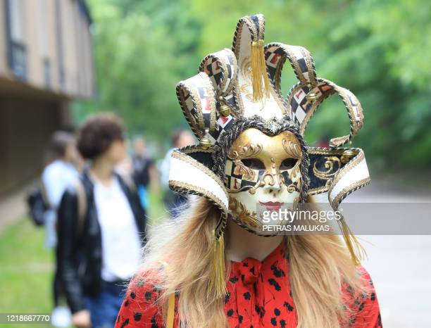 Woman wears a Venice carnival mask during a tourism event to mimicking the Italian holiday experience in Vilnius, Lithuania on June 6, 2020. - With...