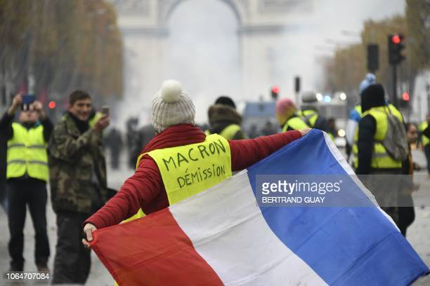 A woman wears a Yellow vest reading Macron resign on the Champs Elysees in Paris on November 24 2018 during a protest against rising oil prices and...