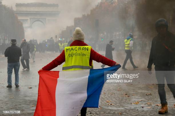 A woman wears a Yellow vest reading Macron resign with a French flag on the Champs Elysees in Paris on November 24 2018 during a protest against...