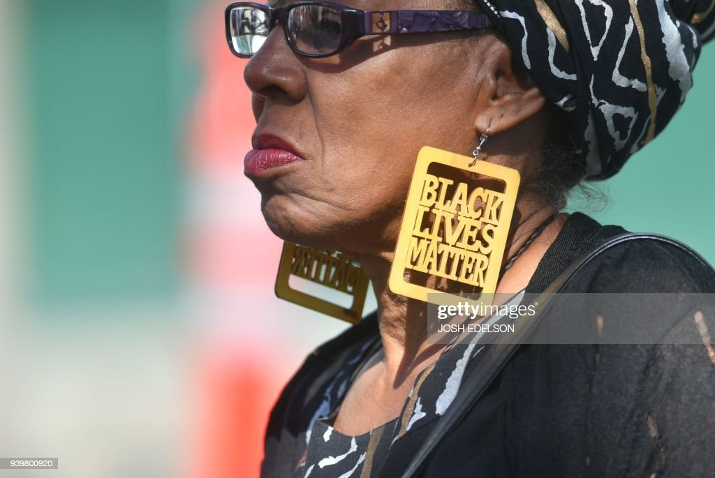 TOPSHOT - A woman wears black lives matter earrings while waiting in line to enter Stephon Clark's funeral in Sacramento, California on March 29, 2018. Stephon Clark, an unarmed African American, was shot and killed by police on March 18, 2018 at his grandmother's home. /