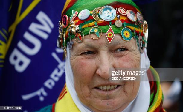 A woman wears different pins on her headscarf among them various Kurdish emblems during a demonstration on the sidelines of a state visit of the...