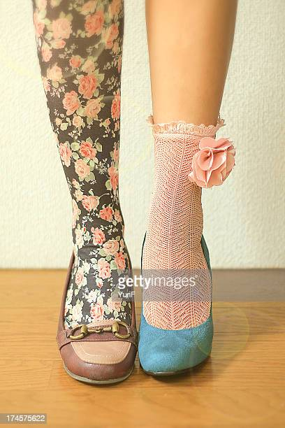 woman wears different socks on each leg - gegensatz stock-fotos und bilder