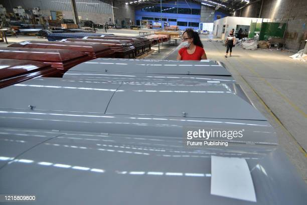 A woman wears face mask as precautionary measure while works in the manufacture of a steel coffin made to closed it hermetically specially design to...