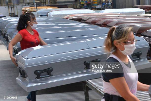 Woman wears face mask as precautionary measure while works in the manufacture of a steel coffin made to closed it hermetically, specially design to...