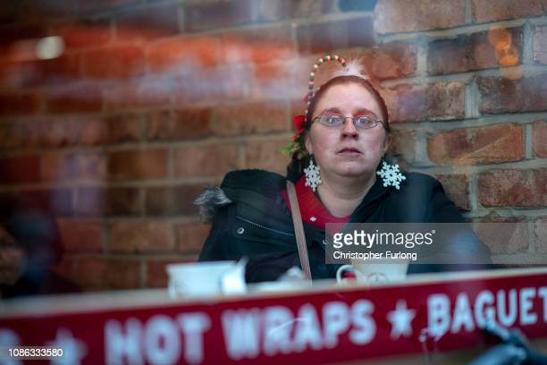 A woman wears festive earrings as shoppers make their last minute purchases on Christmas Eve on December 24 2018 in Birmingham England Financial...