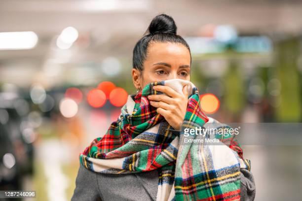 女性はコロナウイルスパンデミック中に覆う代替顔として彼女のチェック柄のスカーフを身に着けている - ゲートル ストックフォトと画像