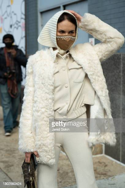 Woman wears Prada sunglasses, DVF cream jacket, Fendi bag with a matching Proenza Schouler shirt and pants outside of Spring Studios during New York...