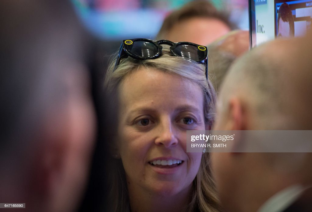 A woman wears Snap Spectacles during the Snap Inc. IPO at the New York Stock Exchange, March 2, 2017 in New York. Snapchat surged in its debut trade Thursday, jumping more than 40 percent from the level set in the initial public offering Wednesday night. / AFP PHOTO / Bryan R. Smith