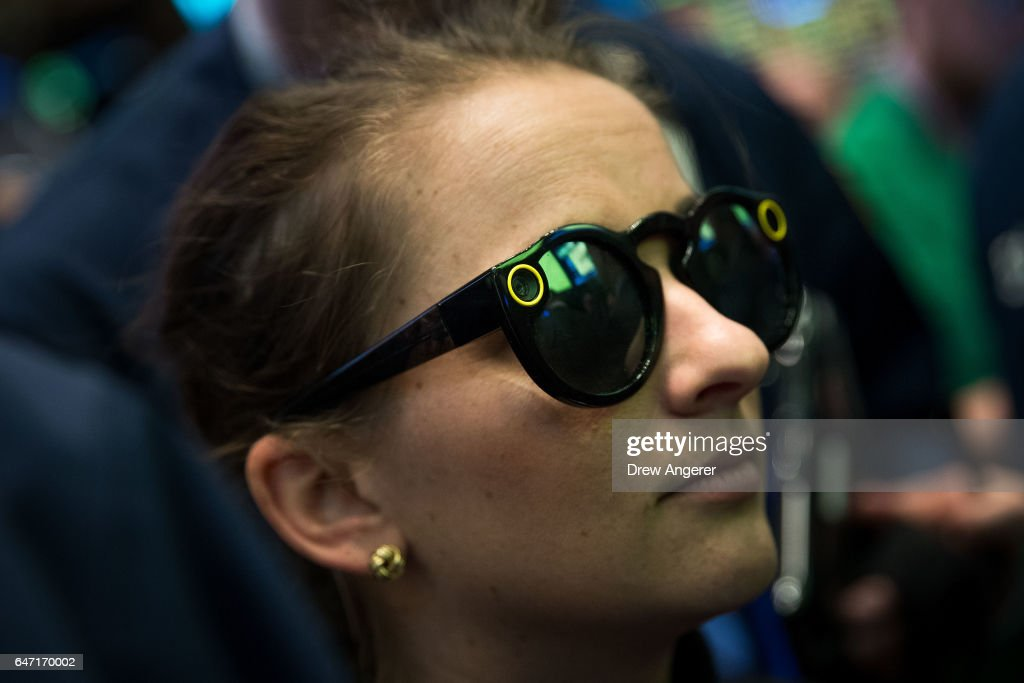 A woman wears 'Snapchat Spectacles' on the floor of the New York Stock Exchange (NYSE), March 2, 2017 in New York City. Snap Inc. shares opened at 24 dollars per share on the NYSE.