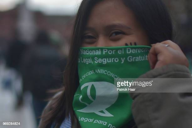 A woman wears the green handkerchief that symbolizes the abortion rights struggle during a protest as part of the 'Not One Less' movement demanding...