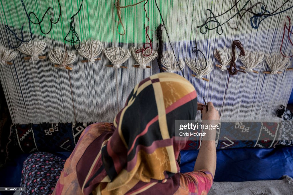 A woman weaves a carpet on August 10, 2018 in Dosemealti, Turkey. Turkey is famous for its artisan carpets but before they are sent to stores, masses of handmade carpets, flat woven kilims and embroidered rugs from all over Turkey are sent to the Dosemealti district in Antalya. The carpets are laid out in the sun and are turned regularly to soften the colors and give them an antique look. Turkey's carpet industry employs more than 40,000 people and exports have risen in the past five years to more than 10bn USD .