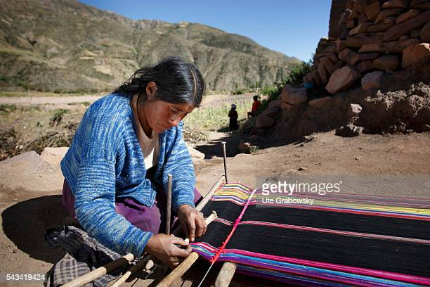 A woman weaves a traditional cloth on a loamy ground on April 16 2016 in Tarwachapi Bolivia