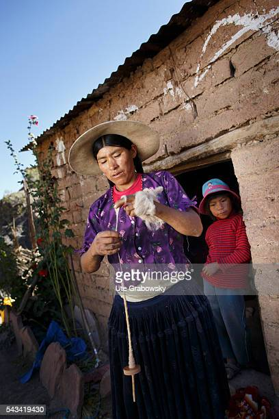 A woman weaves wool with a hand spindle in front of her hut on April 16 2016 in Tarwachapi Bolivia