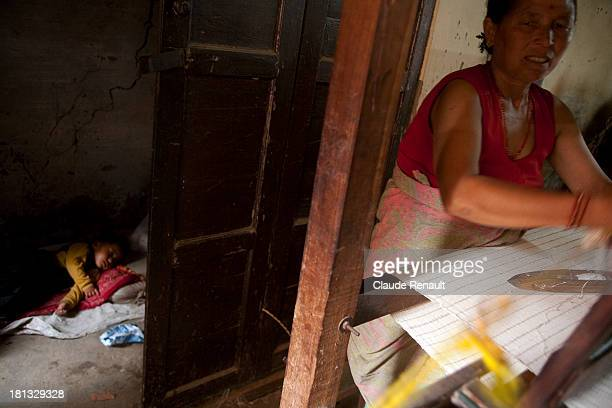 CONTENT] A woman weaving inside a small workshop while her baby is sleeping in Bhaktapur