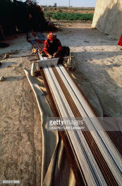 Woman weaving on a loom in a village along the Euphrates river Syria